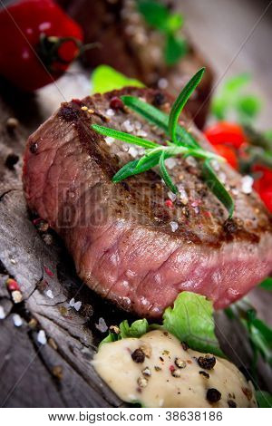Medium grilled bbq steak with fresh herbs and tomatoes