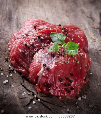 Raw beef steaks on wooden table