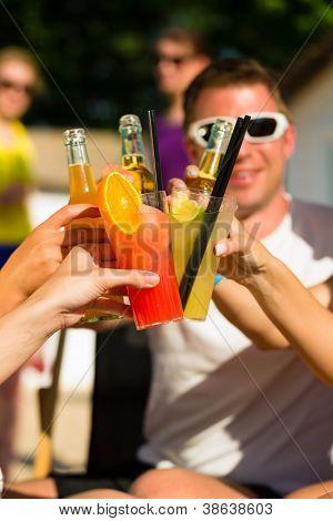 Personas en la playa bebiendo una fiesta, amigos el tintinear de vasos con cócteles y cerveza que se divierten