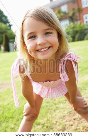 Portrait Of Young Girl Standing In Garden Wearing Swimming Costume