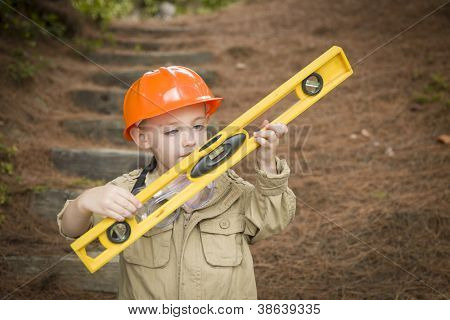Happy Adorable Child Boy with Level, Hard Hat and Goggles Playing Handyman Outside.
