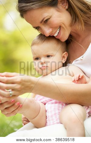 Mother Sitting With Baby Girl In Field Of Summer Flowers