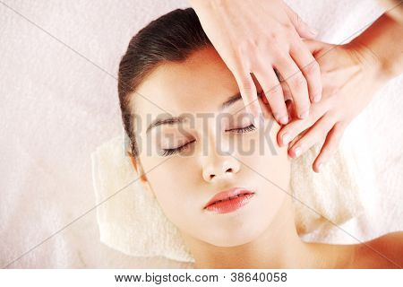 Beautiful young relaxed woman enjoy receiving face massage at spa