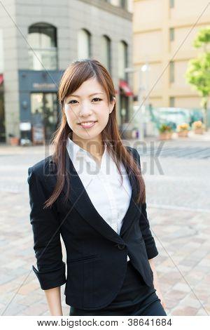 Beautiful business woman walking outside her office. Portrait of asian.