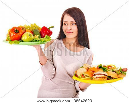 Woman choosing between healthy and unhealthy eating.