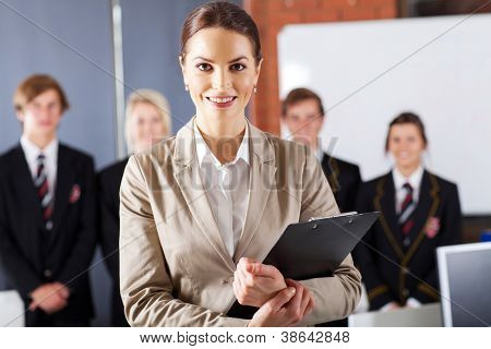 female high school teacher in classroom with group of students