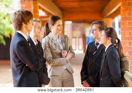 high school teacher talking to students in corridor