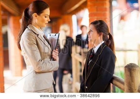 High School-Lehrer im Gespräch mit Studentin außerhalb der Klassenzimmer