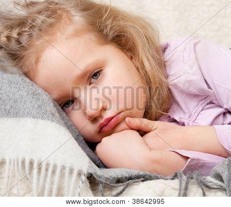 Niño de la enfermedad. Niña, envuelta en una cobija