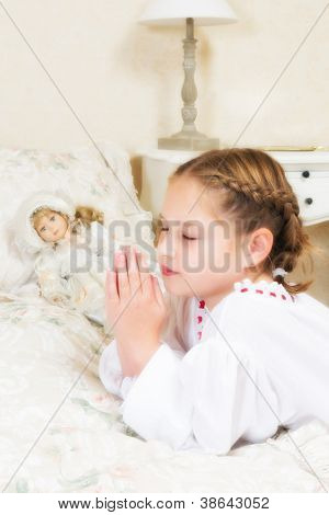 Vintage little girl saying her prayers in her bedroom, beside her antique doll