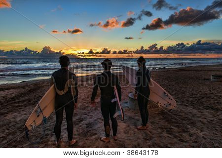 OCEANSIDE, CALIFORNIA - OCT 11: 3 unidentified surfers look for one last wave and admire a Pacific Ocean sunset on October 11, 2012 in Oceanside, California. Oceanside is 40 miles north of San Diego.