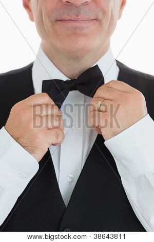 Smiling waiter adjusting his bow tie