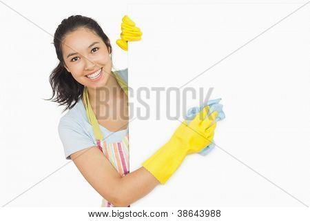 Mujer alegre limpieza superficie blanca en el delantal y guantes de goma