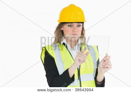 Female architect touching on a pane while holding it