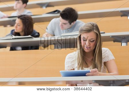 Student sitting at the lecture hall while holding a tablet pc and usig it to take notes