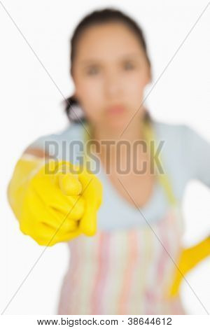 Woman in apron and gloves pointing accusingly ahead