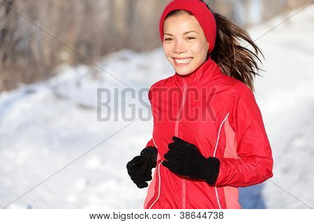 Fitness running woman in winter. Runner closeup of happy active sport model jogging in snow in winter forest. Beautiful mixed race asian chinese caucasian female model.