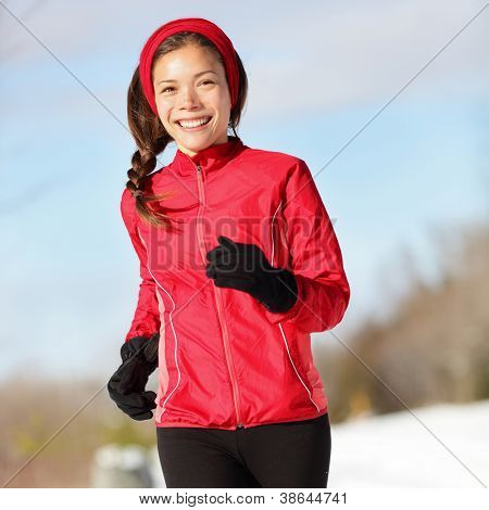 Fitness running woman. Closeup of female runner training and jogging outdoors in winter snow. Wellness workout and healthy lifestyle concept with mixed race Asian / Caucasian female fitness model.