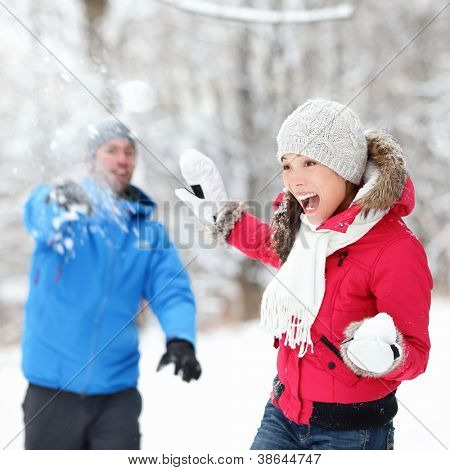 Winter fun - couple in snowball fight having fun together in forest snow landscape. Happy young interracial couple playing together in the snow.