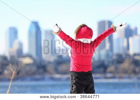Happy winter woman in city excited and cheering with arms raised in happiness. Beautiful young woman and Montreal City skyline, Quebec, Canada.