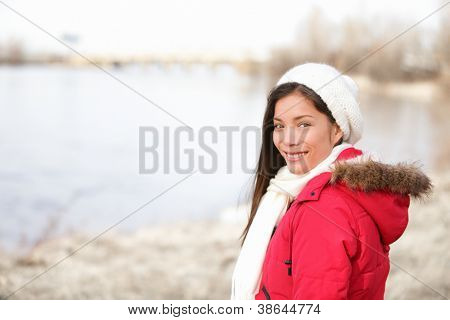 Winter woman portrait outside. Mixed-race girl smiling happy in cold winter landscape wearing winter clothing smiling happy looking at camera. Asian Chinese and Caucasian ethnicity. Quebec, Canada.