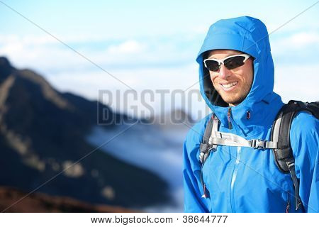 Hiker man trekking portrait in high mountain. Hiking male in alpine clothing hard shell jacket above in mountain above the clouds. Portrait of young man outdoorsman.