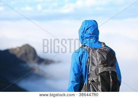 Hiker looking at view in high altitude mountain above the clouds. Mountaineer man enjoying view at summit top in alpine wear with backpack.