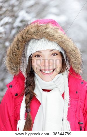 Portrait of winter woman smiling happy and cheerful outside in snow winter forest. Beautiful mixed-race Asian Chinese / Caucasian female model.