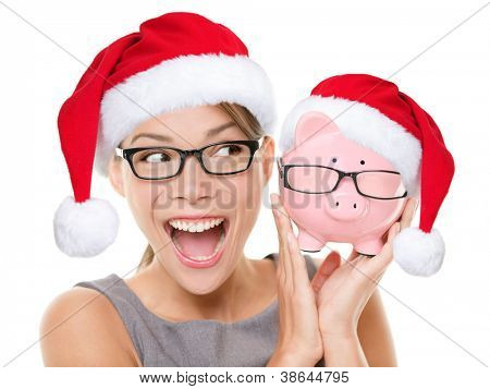 Christmas glasses eyewear sale concept. Woman wearing eye glasses and santa hat is holding piggy bank with glasses. Excited multiracial young woman isolated on white background.
