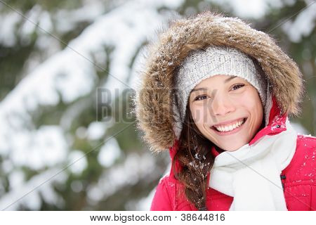 Winter woman portrait outdoors in snow forest. Smiling happy multiracial Asian / Caucasian female model blissful and content looking at camera on cold snowy winter day outside.