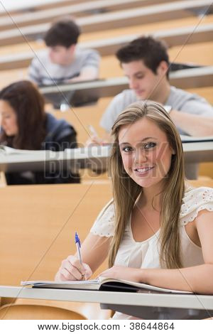 Woman sitting while smiling at the lecture hall and taking notes