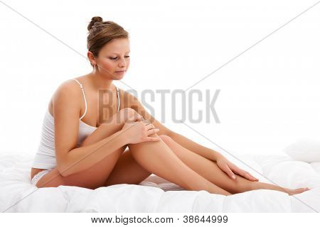 Beautiful, slim woman sitting on white background