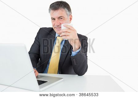 Businessman with a laptop is drinking coffee at his desk on a white background