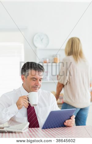 Man sitting at the kitchen holding a cup of coffee and using tablet pc before work