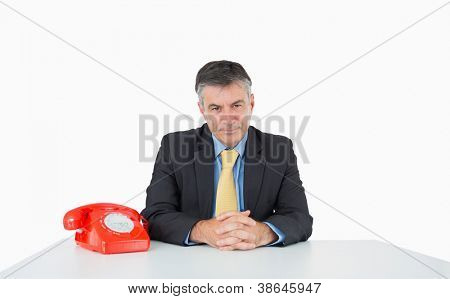 Calm man sitting at his desk with a phone on a white background