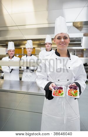 Chef presenting her salads in kitchen with team behind her