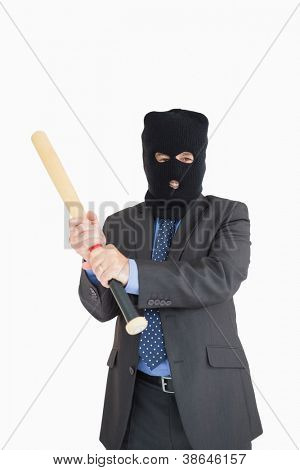 Smiling businessman holding a baseball bat and wearing a balaclava