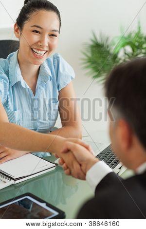 Happy businesswoman shaking man's hand in her office