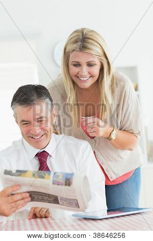 Couple reading a newspaper at the kitchen together before work