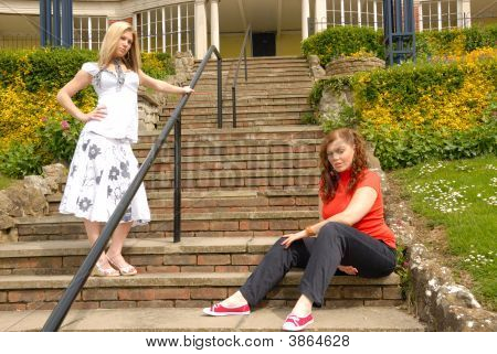 Two Girl Friends On Steps In The Park