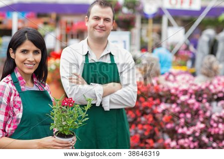 Two smiling garden center employees standing in garden center