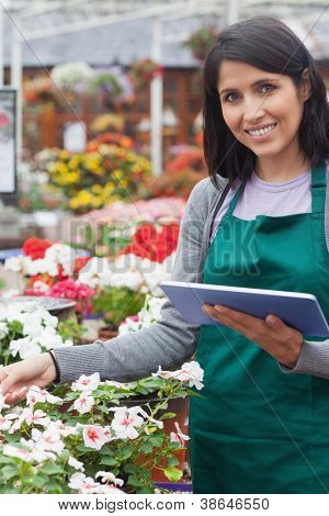 Smiling worker checking flowers in garden center with tablet computer