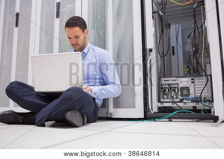 Man sitting on floor with laptop beside servers in data center