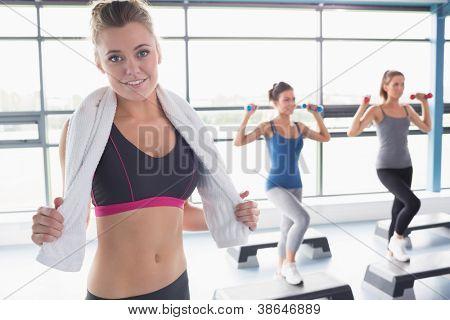 Frau lächelnd an Vorderseite des Aerobic-Klasse im Fitness-Studio