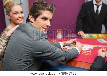 Couple smiling as man is taking his winnings in casino