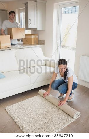 Woman laying out rug with man holding moving boxes in living room