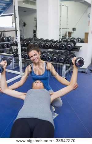 Cheerful female trainer helping woman lifting weights in a fitness studio
