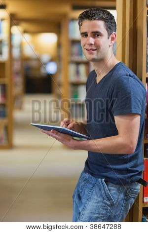 Man leaning at a wall at the library holding a tablet PC smiling