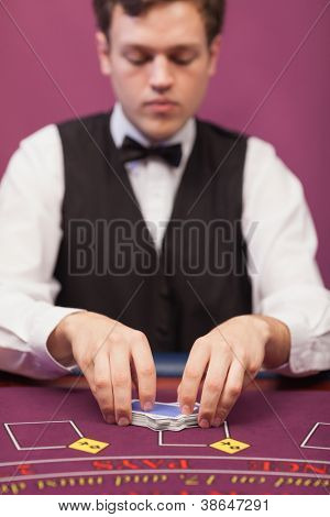 Dealer shuffling the deck of cards at poker table