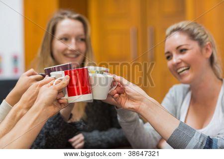 Estudiantes que tintinea tazas sonréiendo en la Universidad